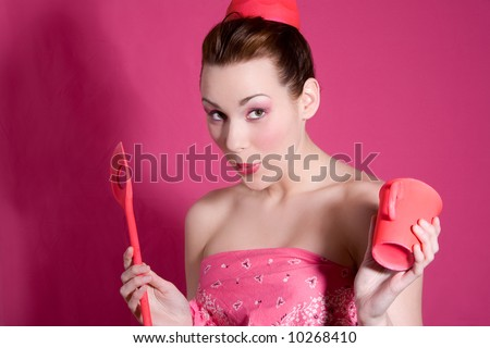 Cute brunette on pink background with a cup and wooden spoon - stock photo