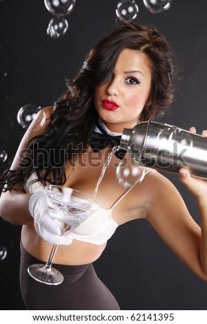 Cute brunette serves a martini among bubbles - stock photo