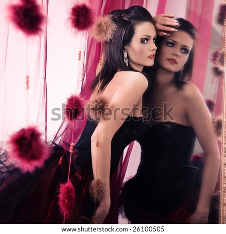 Cute brunette standing at mirror