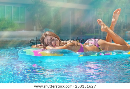 Cute brunette sunbathing by the pool in the sunshine, lying on a blue mattress - stock photo