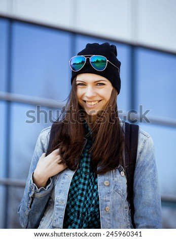 cute brunette teenage girl in hat, student outside smiling - stock photo