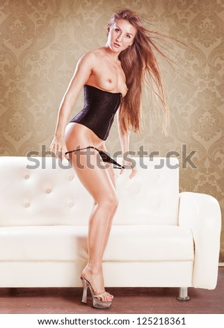 Cute brunette topless woman removing panties at home - stock photo