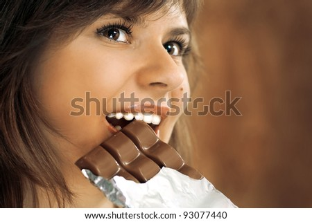 cute brunette with brown eyes eats chocolate - stock photo