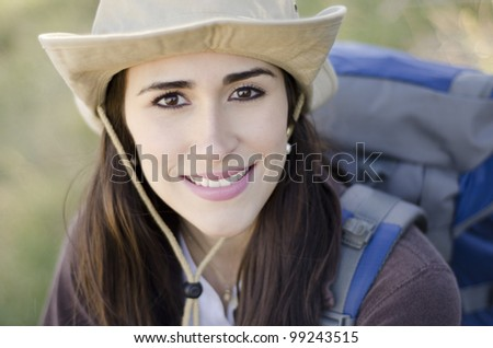Cute brunette with hat and backpack on a hiking trip