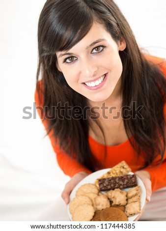Cute brunette woman eating sweet cereal and chocolate biscuits in bed. Adorable and charming model, looking at camera and smiling. - stock photo