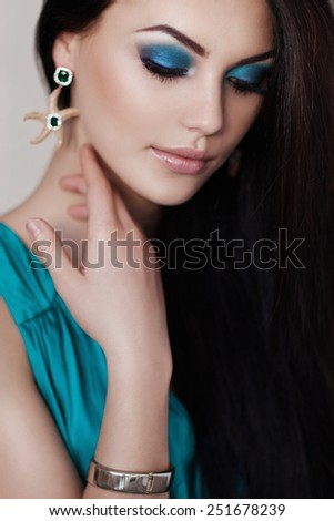 Cute brunette woman in gorgeous emerald dress. - stock photo