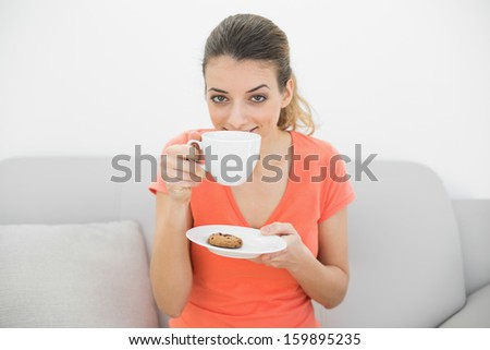 Cute brunette woman smelling a cup sitting on couch looking at camera