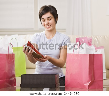 Cute brunette woman surrounded by shopping bags and looking at new shoes. Horizontal.