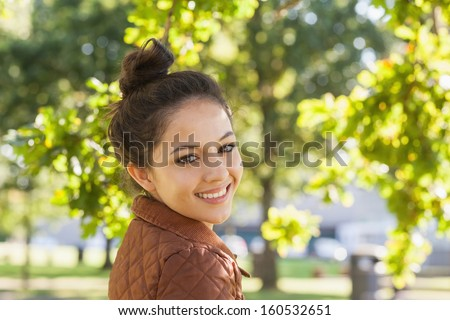 Cute brunette woman wearing a brown coat posing in a park smiling at camera - stock photo