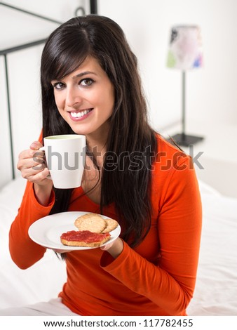 Cute brunette woman with breakfast drinking steaming coffee and holding a plate with biscuits and toast with jam in bedroom. - stock photo