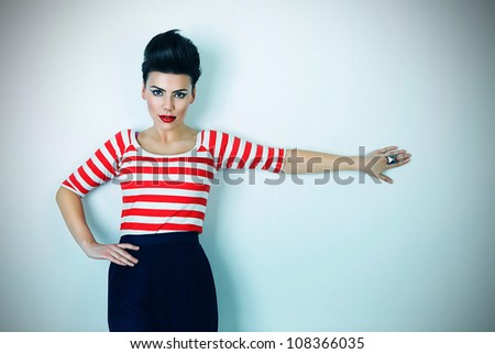 cute brunette woman with hand on wall - stock photo