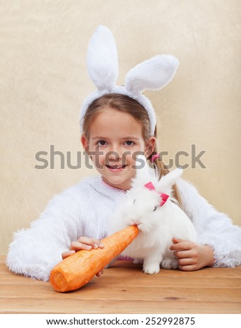 Cute bunnies together - little girl feeding her white rabbit - stock photo