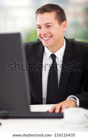 cute business man working on computer in his office - stock photo