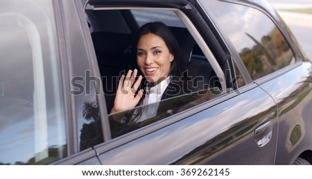 Cute business woman sitting in car waving hand - stock photo