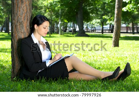 Cute business woman sitting on the grass and making notes, in summer park. - stock photo