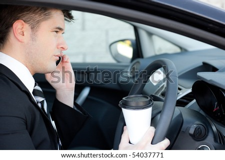 Cute businessman talking on the phone in a car - stock photo