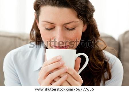 Cute businesswoman enjoying her coffee at home in the living room - stock photo