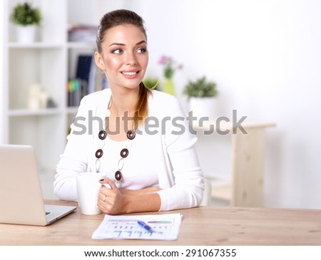 Cute businesswoman holding newspaper sitting at her desk in office . - stock photo