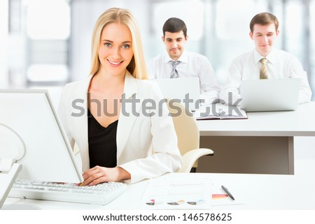 Cute businesswoman in an office with colleagues at the background - stock photo