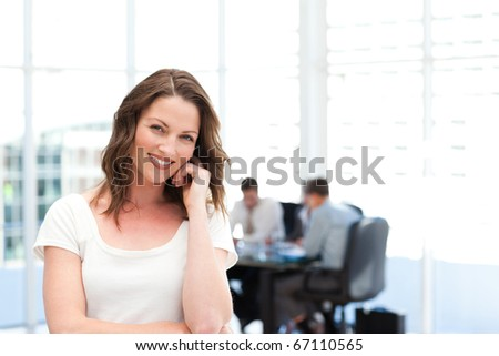 Cute businesswoman standing in front of her team while working in the background