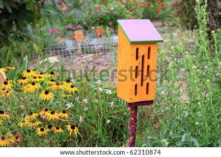 Cute butterfly house in ornamental garden in summer - stock photo