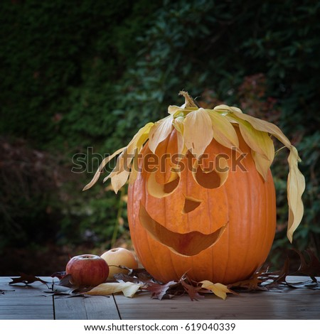 cute carved halloween pumpkin with a silly hat of fall leaves sitting on a table