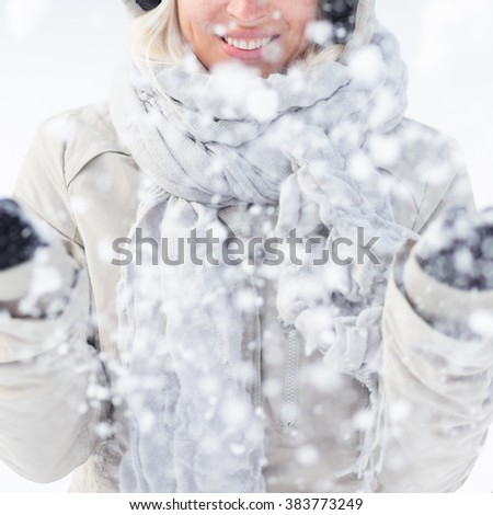 Cute casual young woman playing with snow in winter time. - stock photo