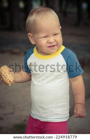 Cute caucasian baby eating corn - stock photo