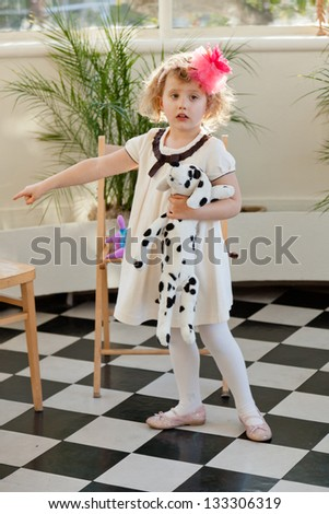 Cute caucasian baby girl in white dress with plush puppy.