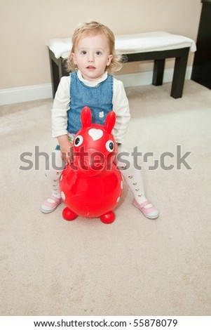 Cute Caucasian baby girl playing on a floor. - stock photo