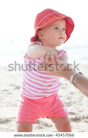 Cute Caucasian baby girl playing with the sand on the beach. - stock photo