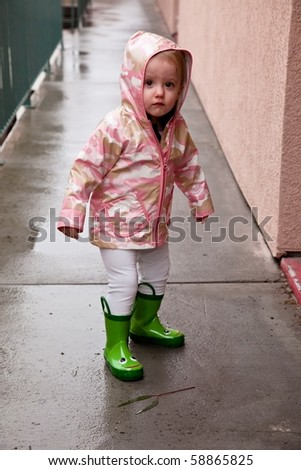 Cute caucasian baby girl wearing pink raincoat and green rubber boots. - stock photo