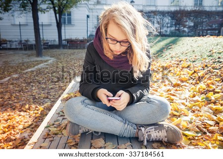Cute Caucasian blond teenage girl in jeans and black jacket sitting on park bench and using smartphone, outdoor autumn portrait. Vintage warm tonal correction photo filter, retro style effect - stock photo