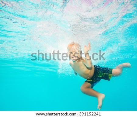 Cute caucasian boy enjoys of swimming underwater - stock photo