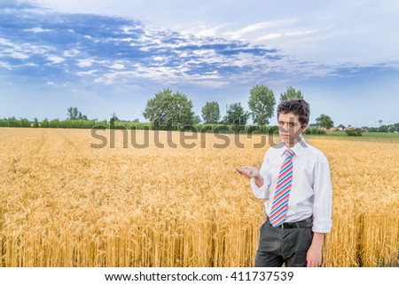 cute caucasian boy in a wheat field in countryside