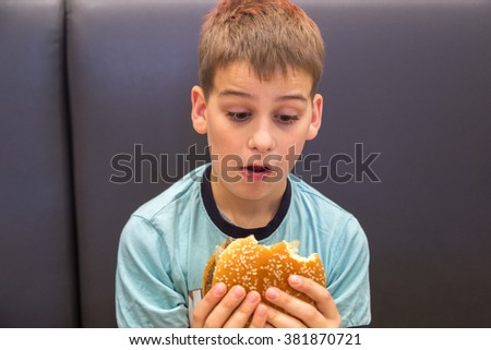Cute caucasian boy is eating big burger