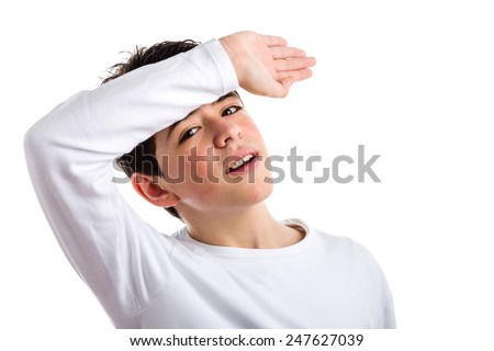 Cute Caucasian boy with acne-prone skin in a white long sleeved t-shirt holding his right arm on the front as protecting from sun or wiping the sweat - stock photo