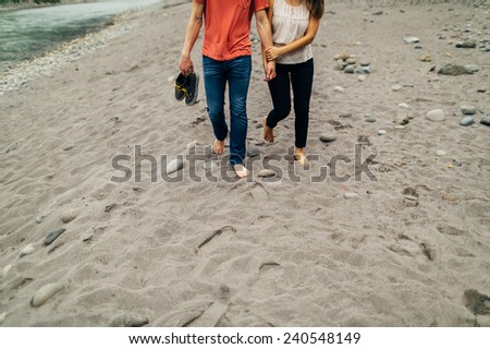 cute caucasian couple on sandy river shore holding hands walking no faces - stock photo
