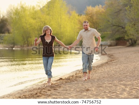 cute Caucasian couple running on beach holding hands
