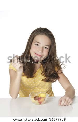 Cute Caucasian girl eating a bowl of fruit - stock photo