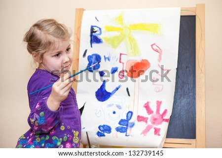 Cute Caucasian girl standing with painting brush near easel