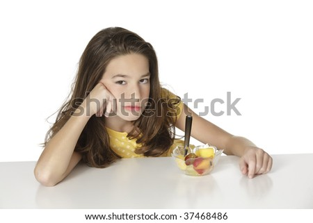 Cute Caucasian girl that very unhappy that she has to eat fruit - stock photo