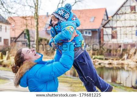 cute caucasian little boy and his mother having fun, outdoors on cold day. - stock photo