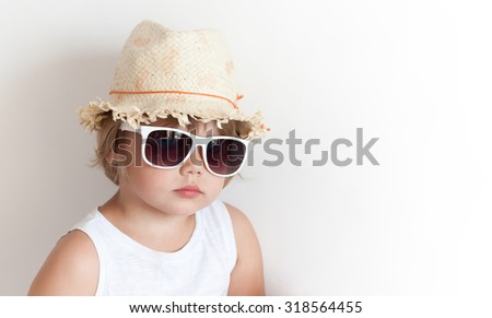Cute Caucasian little girl in straw hat and sunglasses over white wall background - stock photo