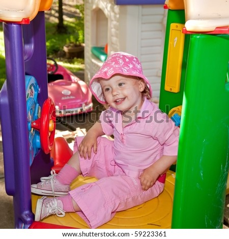 Cute caucasian toddler girl having fun playing on playground.