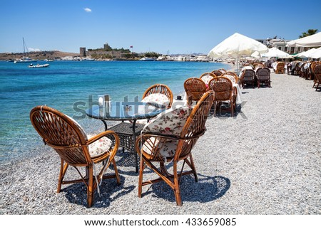 Cute chairs and table on the beach at seaside restaurant in Bodrum, Turkey  - stock photo
