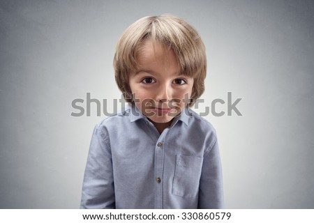 Cute cheeky boy with guilty expression concept for apologetic, regret, making a mistake, innocence or worried - stock photo