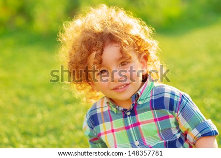 Cute cheerful boy relaxing outdoors, adorable child with beautiful curly hair spending time on green field in garden, summer holidays concept - stock photo
