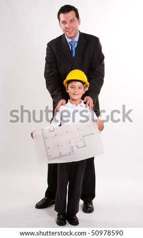 Cute cheerful boy with a safety helmet, holding a plan, with his dad - stock photo