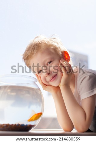 cute cheerful boy with goldfish - stock photo